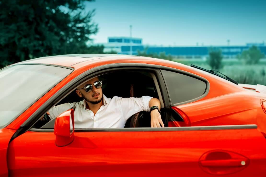 Młody kierowca czerwonego sportowego samochodu