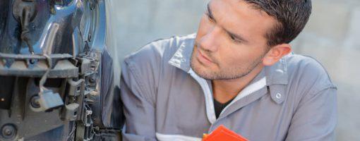 Mechanik zastanawia się nad kosztami naprawy auta po awarii